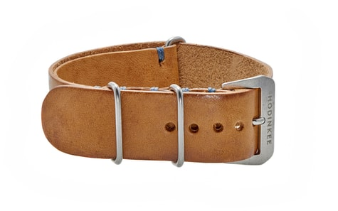 889a53869d8 This Beige Leather NATO Watch Strap features an even beige color with  slight staining at the edges and funky blue contrast stitching.