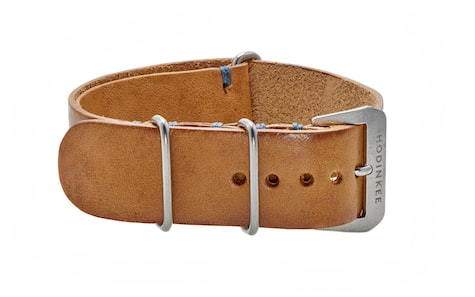 cddd2c2a29f This Beige Leather NATO Watch Strap features an even beige color with  slight staining at the edges and funky blue contrast stitching.